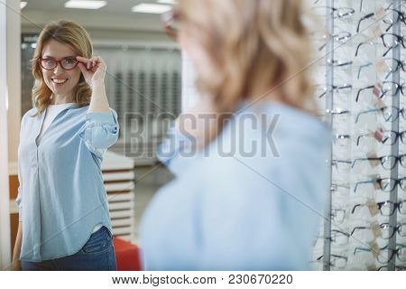 Portrait Of Beaming Female Client Looking At Mirror In Optician Store. Eyesight Correction Concept