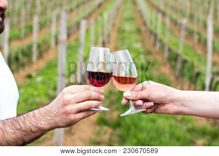 A Man And A Woman Check With Glasses Of Wine. Glasses With Red Wine In The Female And Male Hands. Wi