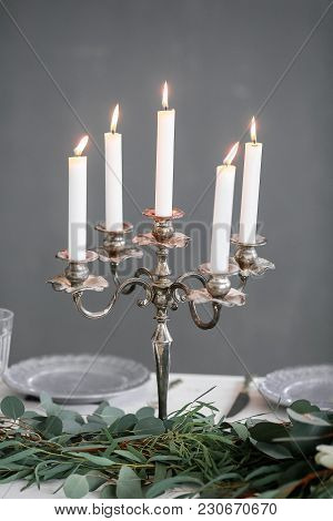 Silver Candlestick And Flowers On A Dinner Table