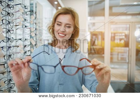 Portrait Of Happy Young Woman Choosing Spectacles In Optical Store. Selection Of Glasses Concept
