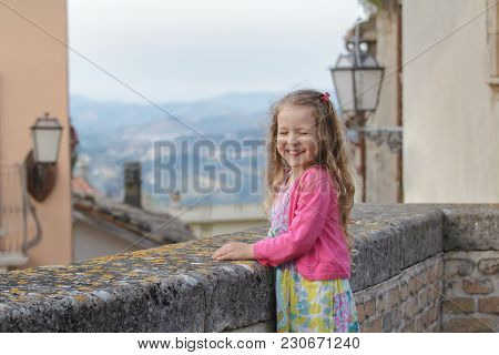 Little Girl Is Laughing And Screwing Up Eyes On City Viewpoint