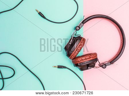 Fancy Headphones Laying On A Flat Pink And Blue Surface. Analog Wire Frames The Table