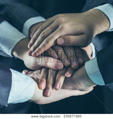 Close-up Of Hands Of Business Teams, Stacked One On Another.photo On A Black Background And Has Spac