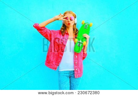 Fashion Woman Listens To Music In A Wireless Headphones Holds Skateboard In Pink Denim Jacket