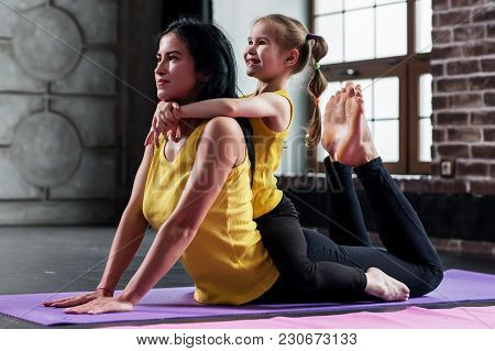 Young Caucasian Woman Doing Stretching Exercise For Spine Together With A Child Sitting On Her Back