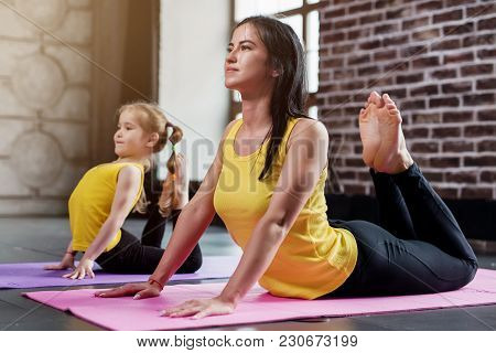 Young Mother And Her Daughter Wearing The Same Sportswear Doing King Cobra Pose During Group Yoga Tr