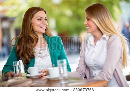 smiling friends relaxing with coffee at café