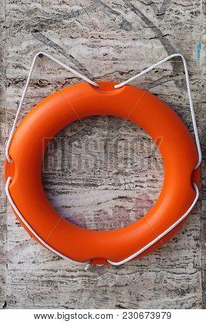 Orange Plastic Life Ring Saver At Wall