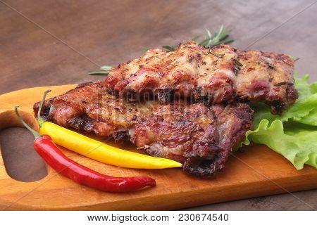 Grilled Barbecued Ribs With Lettuce Leaves, Hot Chili Pepper And Sauce On Wooden Cutting Board