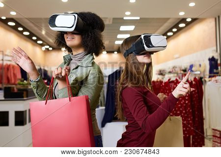 Technological Concept. Two Women In Modern Virtual Reality Headsets Having Expirience In Shopping At