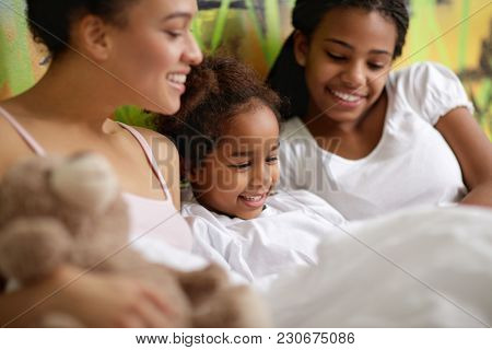 Little Afro-American girl with sisters in bed