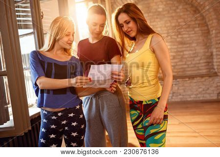 Group of girls reading paper together indoor