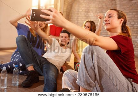 Young female with friends making selfie indoor