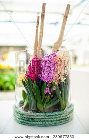 Gorgeous Table Decoration Using Pink, Red, Yellow Flowers Including Small Wooden Sticks In Round Gla