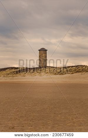 Old lighthouse on the beach with blue sky