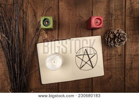 An Overhead Photo Of An Open Grimoire, Candles, A Pine Cone, And A Handmade Broom. Wiccan Ritual Obj