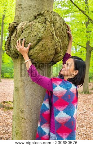 Colombian Woman Holding Cancerous Tumor On Beech Tree Trunk