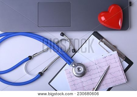 Workplace Of Doctor With Laptop, Stethoscope, Rx Prescription, Glasses And Red Heart And Notebook On