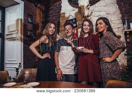 Four Cool Teenagers Wearing Casual Clothes Posing For Camera In A Stylish With Hunting Lodge Interio