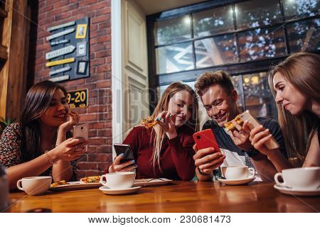 Young People Using Their Mobile Phones Sitting Around The Table Having A Meal In Modern Stylish Cafe
