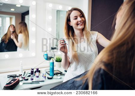 Cheerful Young Makeup Artist Working With A Customer Holding A Thin Brush Standing In Make-up Studio