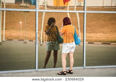 A Young Girl In Shorts Looks At Her Reflection In The Glass Wall.