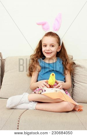 Portrait Of Little Girl In Easter Pink Bunny Ears Holding Toy Chick. Little Girk In Easter Bunny Ear