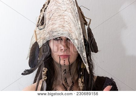 Beautiful Girl Dressed In Witch Or Shaman Halloween Costume With Black Feathers And Crow Head On Whi