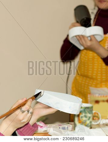 Women Hand With A Paintbrush With Glue Draws In Wooden Form