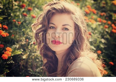 Portrait Of Beauty Woman Poses On Background Bed Of Flowers