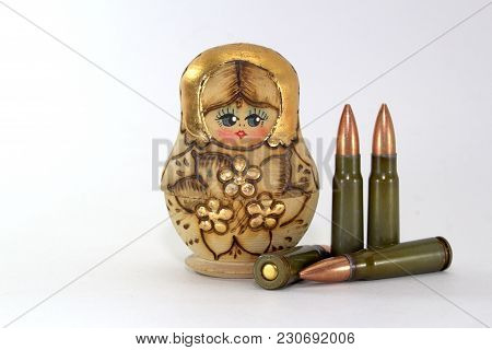 Russian Matryoshka And Several Cartridges For A Kalashnikov Assault Rifle On A White Background Clos