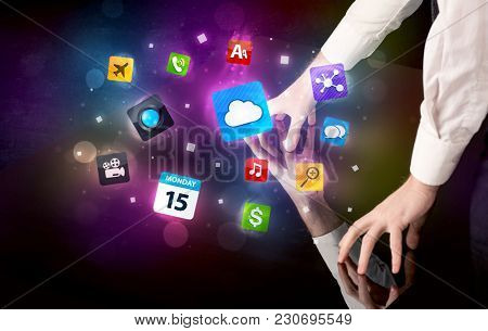 Male hands touching interactive table with colorful application icons on it