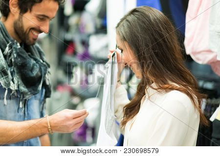 Happy couple shopping in a dress shop
