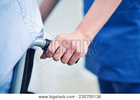 Nurse pushing a patient's wheelchair