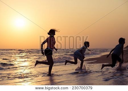 Happy Children Playing On The Beach At The Sunset Time.