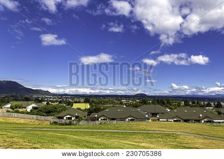 Green And Yellow Grass Lawn, Roofs Of The Houses And The View Of Taupo Town In New Zealand