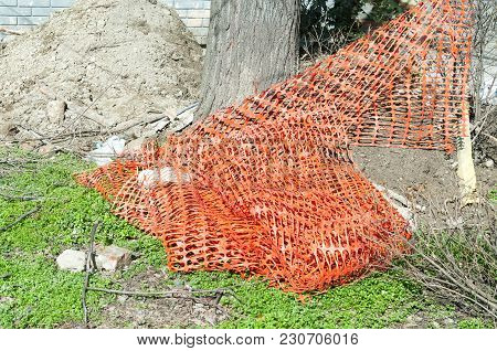 Orange Plastic Safety Net Or Barrier On The Street To Protect Excavating Construction Site