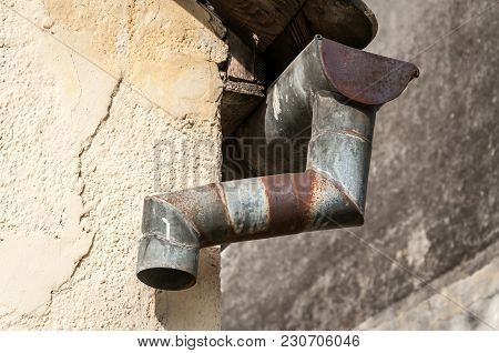 Old And Rusty Rain Gutter On Abandoned House Damaged By Age And Water Close Up