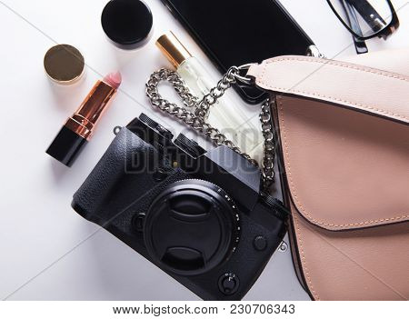 Top view of woman beige bag with accessories smartphone, cosmetics, lasses, camera and perfume on white background.