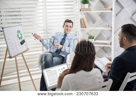 New Concept. Attractive Exuberant Dark-haired Man Sitting In The Chair And Presenting His New Ideas