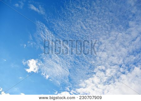 Light Blue sky with white cumulus and cirrus clouds background poster