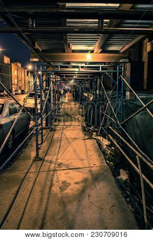 A city sidewalk with construction scaffolding at night