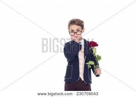 Serious Little Boy In Suit And Eyeglasses Holding Rose Flower And Looking At Camera Isolated On Whit