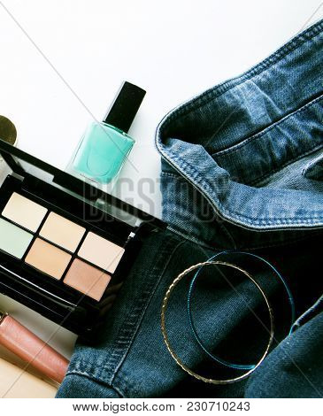 Top view of woman jeans shirt, concealer pallet, lip gloss, nail