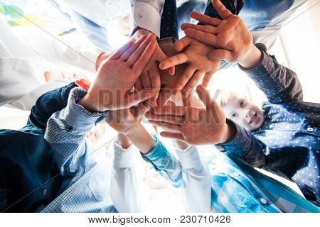 Bottom View Of Young Boys Putting Their Hands Together As A Symbol Of Friendship