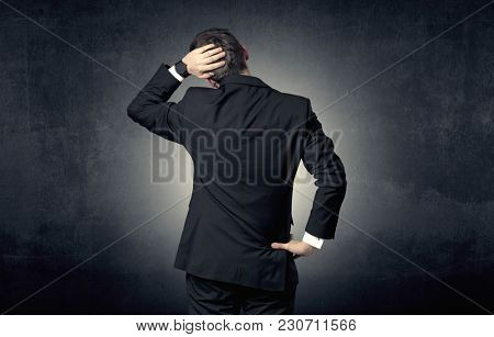 Young businessman standing and thinking alone