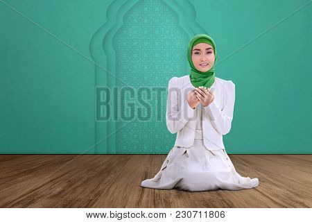 Young Asian Muslim Woman Sitting And Praying