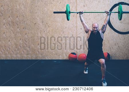 Young Man Athlete Doing Jerks With Barbell With Wall Balls At His Back At Box Gym On A Fitness Routi