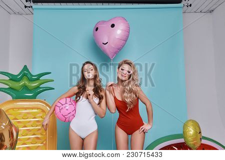 Perfect In Every Way.  Two Playful Young Women In Swimwear Looking At Camera And Smiling While Stand