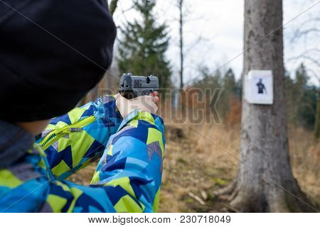 Person With Gun In Hands Shooting On Target On Tree